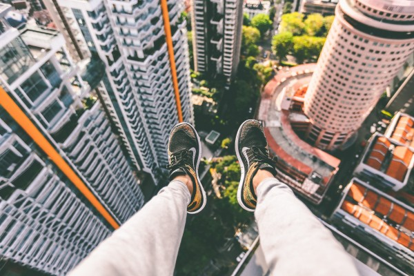 unsplash - man dangling over city